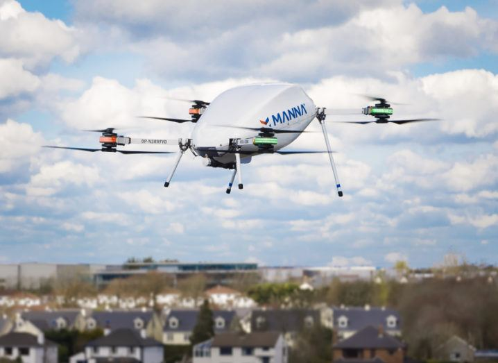 A white drone pictured against a mostly sky background, flying over suburban houses.