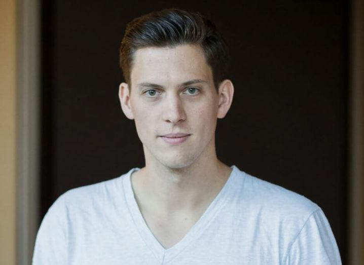 A young man with slicked-back hair wearing a white v-neck T-shirt.