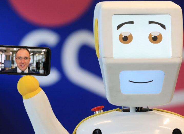 Stevie, a white robot with a smiling face, appears to be holding a smartphone. On the screen of the phone is Minister Robert Troy, wearing a suit.