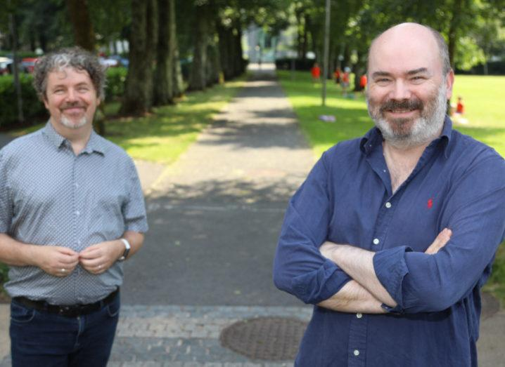 Prof Charles Spillane and Dr Aaron Golden stand outdoors with green grass and trees behind them.