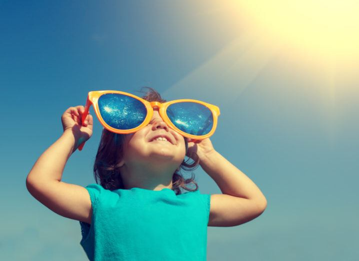 A small child wearing oversized sunglasses beams with joy as she soaks up some sunshine.