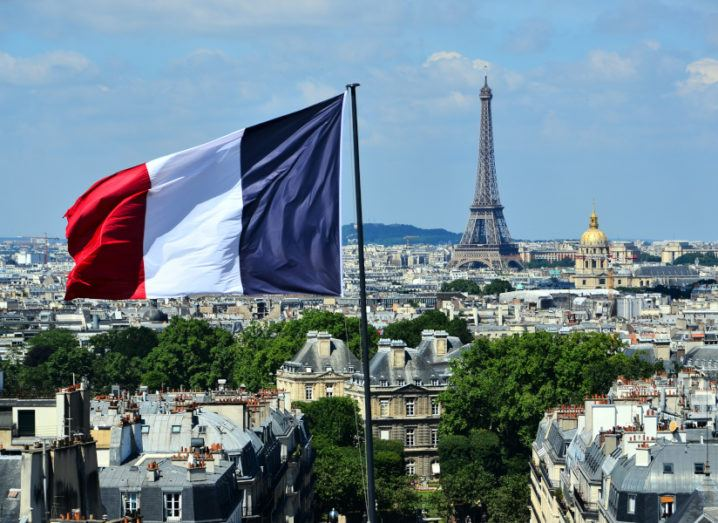 Rooftop view of the city of Paris, taking in the Eiffel Tower and a large French flag flying in the foreground.