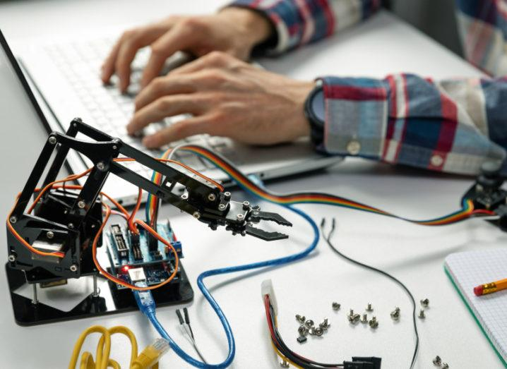 Shot of an engineer's hands working on a robotics project with various robotics and technical equipment laid out beside him on a desk beside a notebook and pencil.