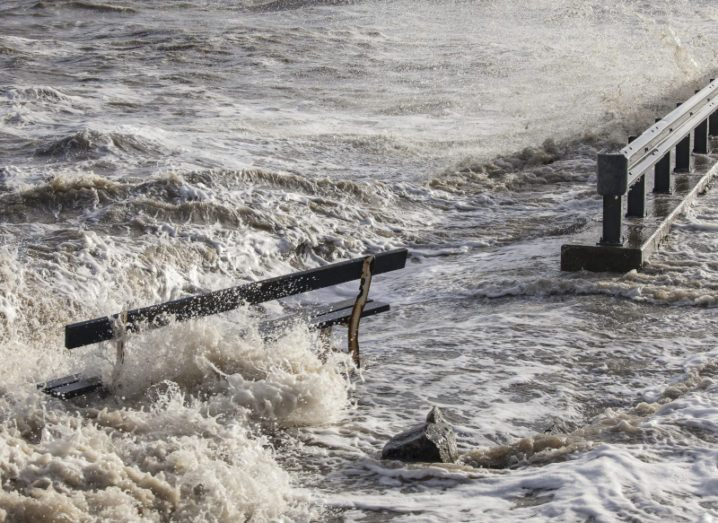 A flood surges over a bench next to a road.