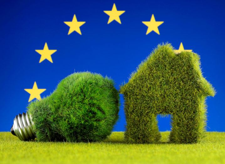 A lightbulb lies beside a miniature model of a house. Both are covered in green grass-like material. The background represents the EU flag with a ring of golden circles on a ground of blue.