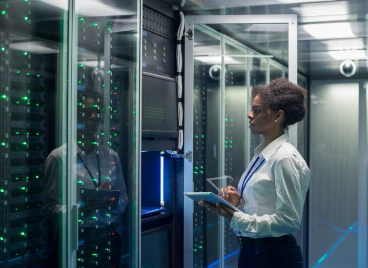 Stock photo of a technician working on a tablet in a data centre full of rack servers.