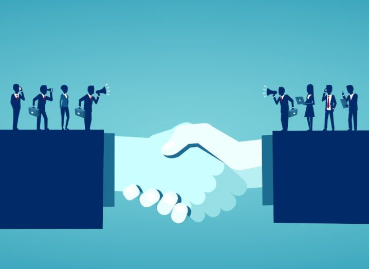 Illustration of hands joined in a handshake, signifying a business deal. Silhouettes of businesspeople holding phones, briefcases and laptops stretch across each arm.