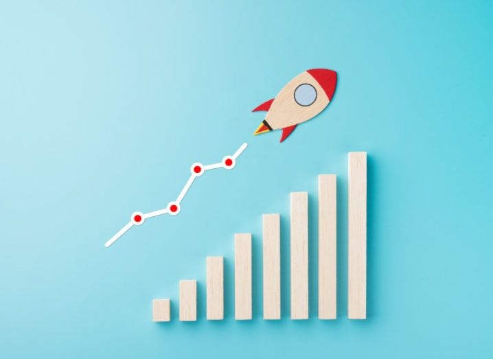 A model of a rocket ship shown blasting off above a representation of a business growth chart, with heightening bars and an upward trend line.