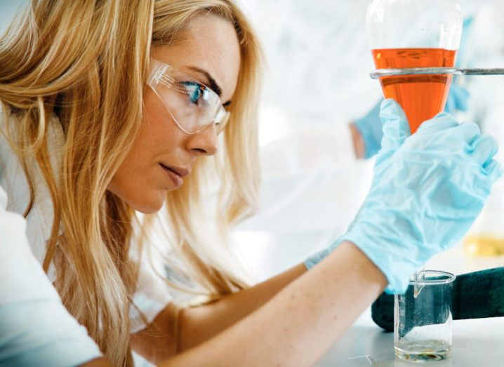 Woman in a lab coat and safety glasses leans over a workstation to concentrate on measuring a liquid in a glass beaker held in place by a clamp.