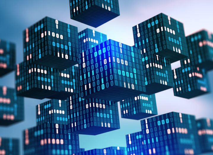 Illustration of blocks of digital information floating across a soft blue background. Each facet of the cubes shows binary code with some ones and zeroes lighting up.