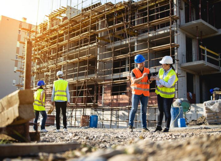 Two groups of two construction workers discussing project plans on a building site.