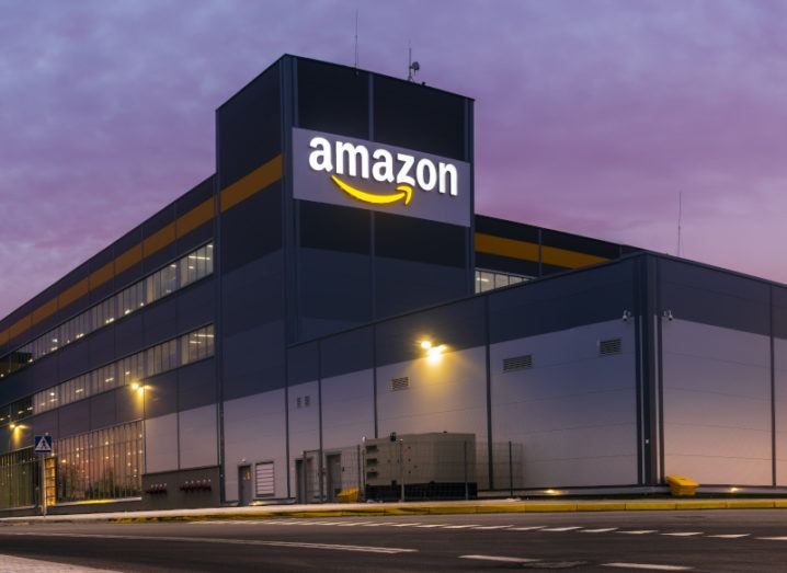 The Amazon logistics centre in Szczecin, Poland, with a purple sky behind it.