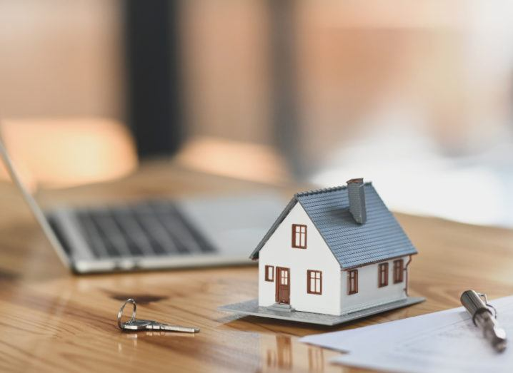 A stock image of a model house beside a key, a laptop, and several documents.
