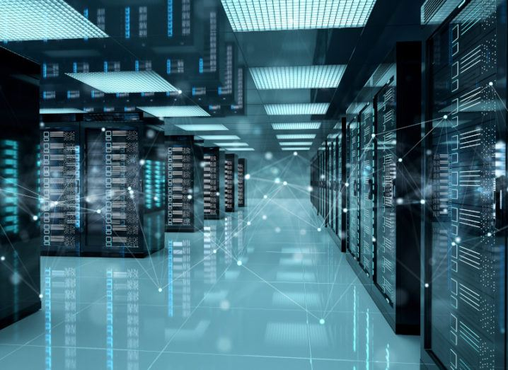 3D rendering of a data centre lit with blue light. There are many rows of servers lined up.