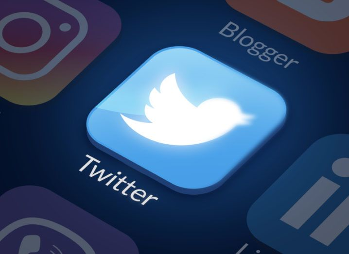 Close-up of the Twitter app icon on a smartphone screen. The icon is a round-cornered square in blue with a white bird silhouette.