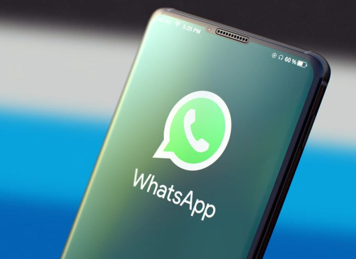 Close-up of a smartphone screen displaying the WhatsApp logo, a bright green speech bubble containing a telephone handset icon.