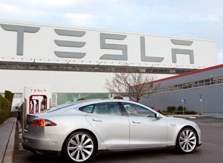 A silver Tesla Model S electric car charging at a tall white chargepoint in the car park of a large factory with the Tesla logo branded on its walls.