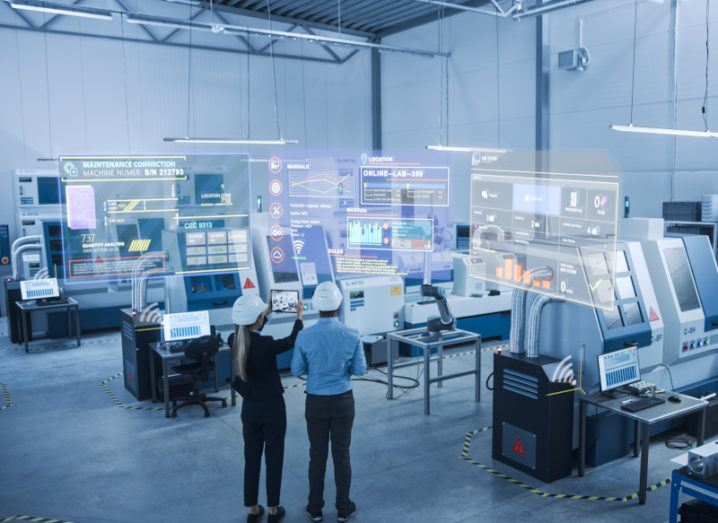 Two engineers stand on a factory floor wearing hard hats. Illustrations of digital interfaces emerge from the nearby equipment, demonstrating the digitisation of the manufacturing process.