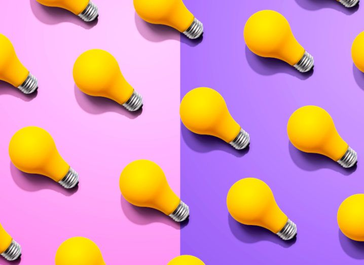 A number of yellow lightbulbs lined up in neat rows on a half pink, half purple background.