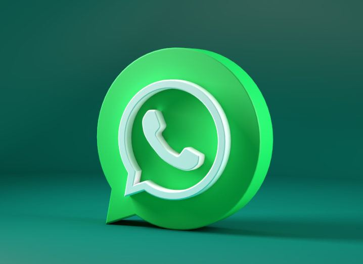 A 3D model of the WhatsApp logo, a green speech bubble containing a phone symbol, stands upright on a darker green surface.