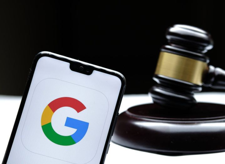 A gavel sits behind a smartphone displaying a G from the Google logo.