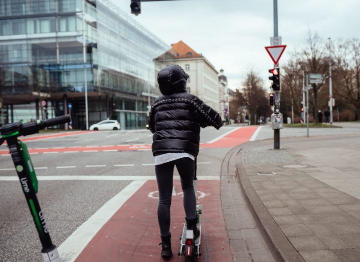 Woman rides an e-scooter on a city cycle lane surrounded by a city scape