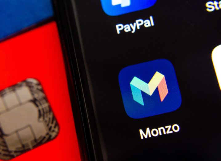 Close-up of the Monzo app with a large M on a smartphone screen. Behind the smartphone, the chip on a red Monzo debit card is just visible.