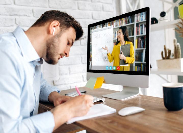Man working at a computer taking notes as he listens to a woman speaking on screen.