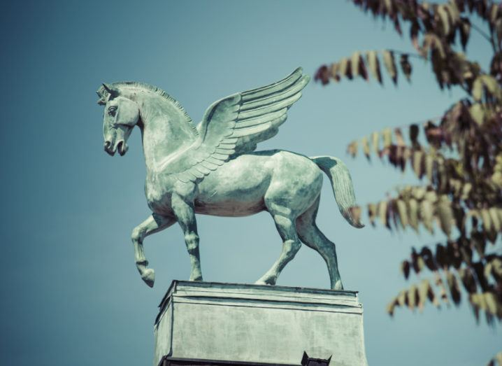 Stone statue of a pegasus, a winged horse, mid-pace.
