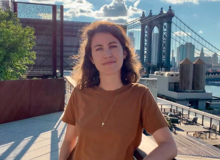 A woman leans on a railing on a sunny day against a cityscape.