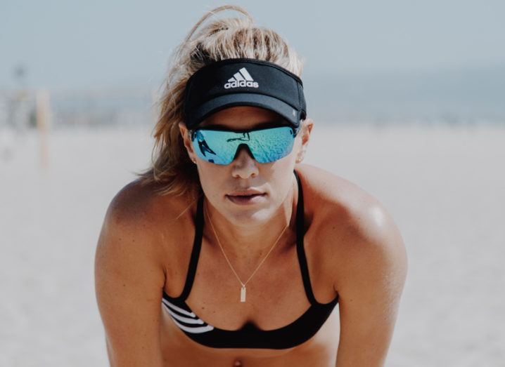 Olympic athlete Alix Klineman leans forward with her hands on her knees. She is on a beach wearing volleyball apparel, including a visor and sunglasses.