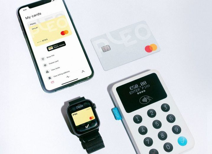 A smartphone lying on a table with the Pleo app open, beside a Pleo-branded card and a payment terminal.