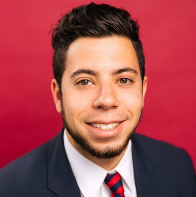A close-up headshot of a man in a suit against a red background.