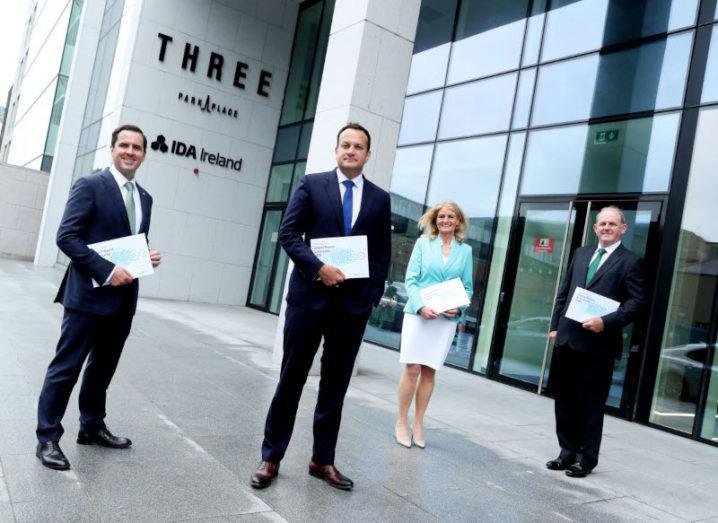 Four people stand socially distanced outside a large building. Each of them is holding a copy of the IDA's mid-year report.