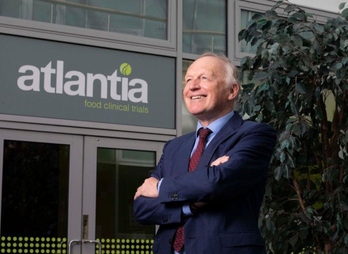 Prof Ted Dinan stands with his arms folded in front of the entrance to Atlantia Clinical Trials. He is looking off to the distance and smiling.