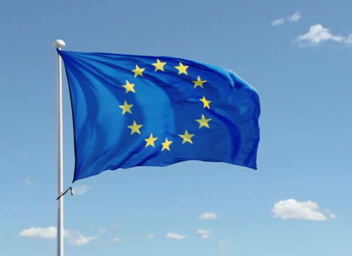 An EU flag blows in the breeze against a blue sky on a sunny day.