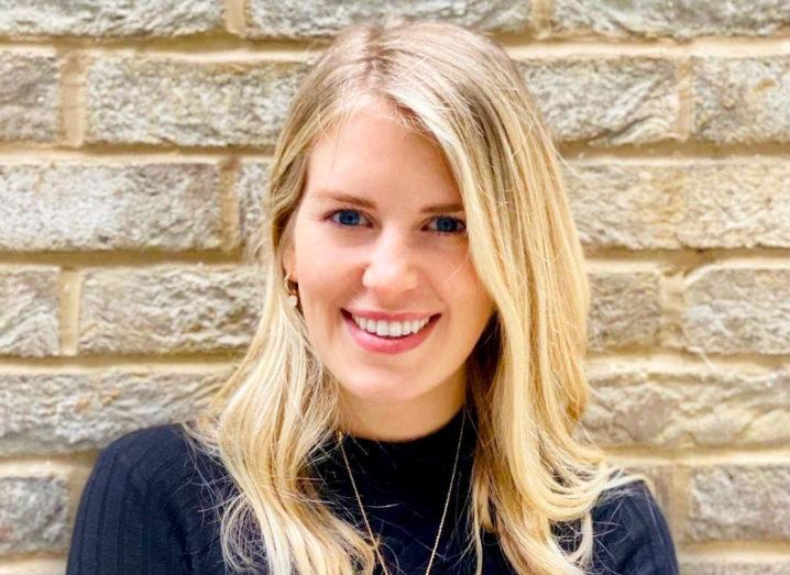 A blonde woman, Ellen Moeller of Stripe, smiling at the camera against a brick wall while wearing a black jumper.