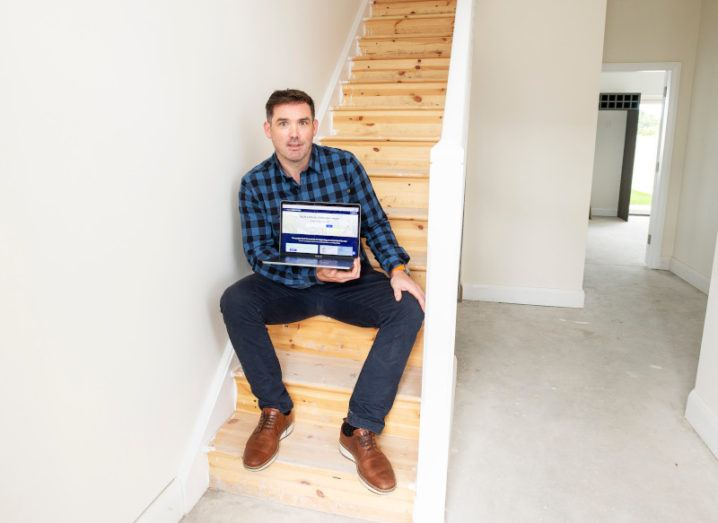Eoghain Ryan, co-founder of Housebuild.ie, pictured sitting in a stairwell holding a laptop.