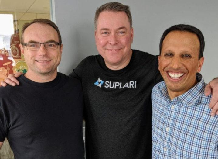 Suplari co-founders Jeff Gerber, Brian White and Nikesh Parekh stand with their arms around each other.