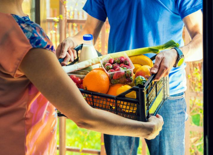 A man handing over a box of groceries to a woman at a door. The box contains an assortment of fruit, vegetables and milk.