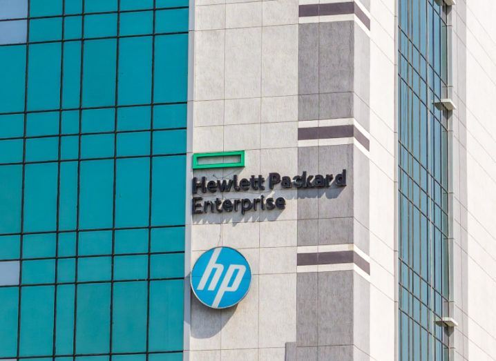 A HPE office building is photographed. The building is a grey-cream colour, with large windows. The HPE logo is on the side of the building.