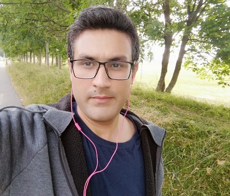 A selfie of a man out on a walk among some greenery. He wears casual clothes and has earphones in his ears.