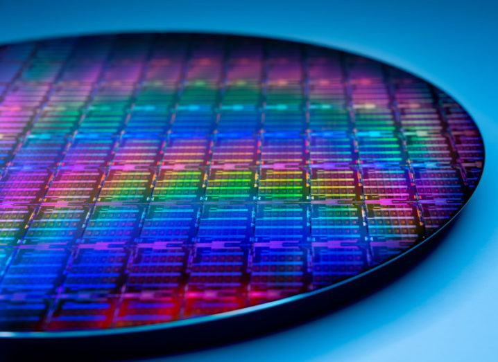 A thin disc of silicon wafer reflecting a full spectrum of colour on its surface.