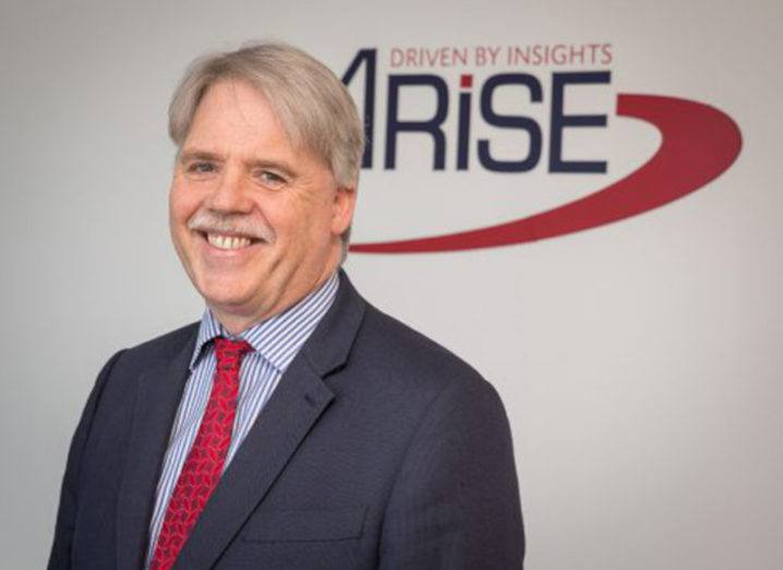 Joe Cahalane, managing director of Arise Europe, stands in front of the company's logo on a white background.