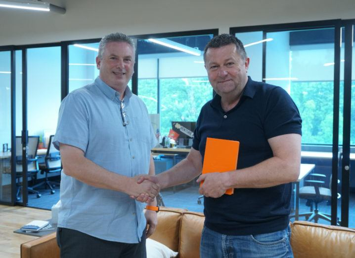 Two men shake hands in an empty office. One holds an orange booklet.