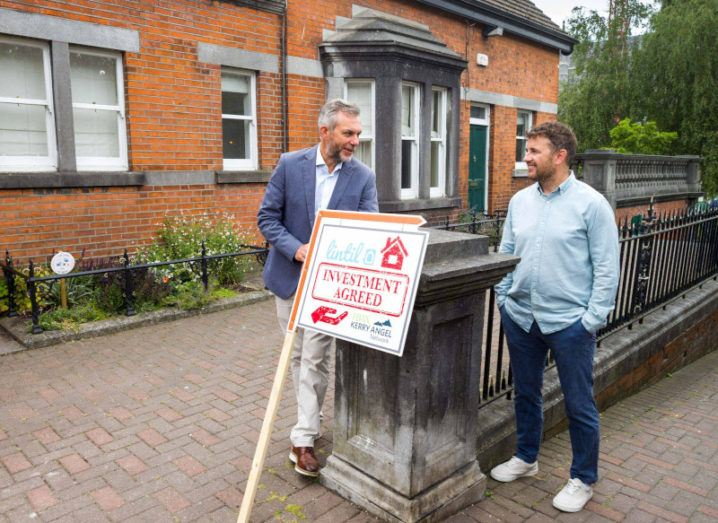 Kerry Angel Network chair Sean Ryan and co-founder and CEO of Lintil Emmet Creighton pictured outside a red brick house with a sign bearing Lintil's logo.