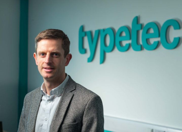 A man in a suit smiles at the camera in front of a wall with the Typetec logo displayed on it.