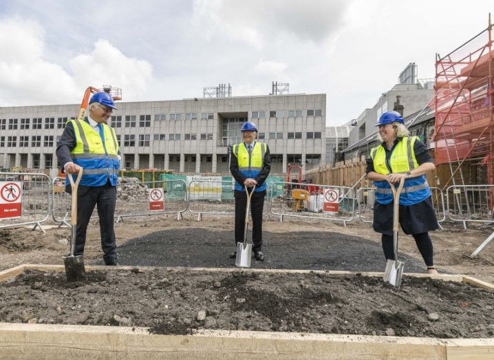 Three people in high-vis vests and hard hats stand with shovels at a building site on the Trinity College Dublin campus.