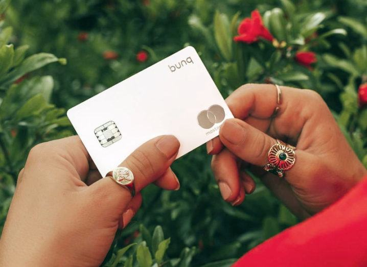 A woman's hands holding a metal debit card bearing the Bunq and Mastercard logos.