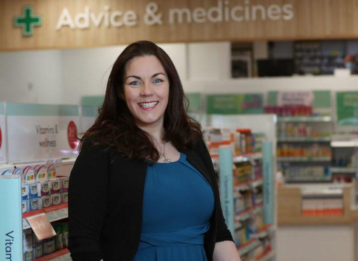 A woman with dark hair wearing a blue dress and a black cardigan stands in a Boots pharmacy. She is smiling at the camera.